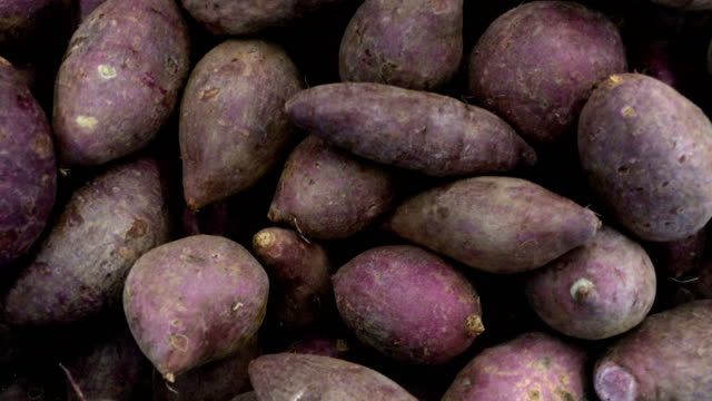 fresh purple yams pile put in basket selling at the market, 4k. - purple stock videos and b-roll footage