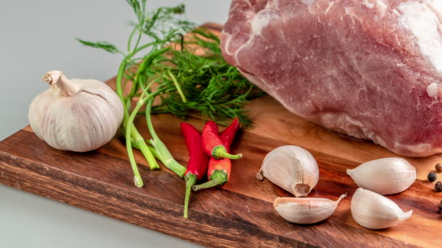 fresh raw pork meat steak with hot sweet pepper dry spices castor and pepperbox on wood cutting boar over table - raw food stock videos & royalty-free footage