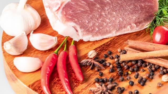 vidéos et rushes de steak de viande fraîche de porc cru avec poivron chaud sec castor épices et pepperbox sur sanglier de bois coupe sur table - aliment cru