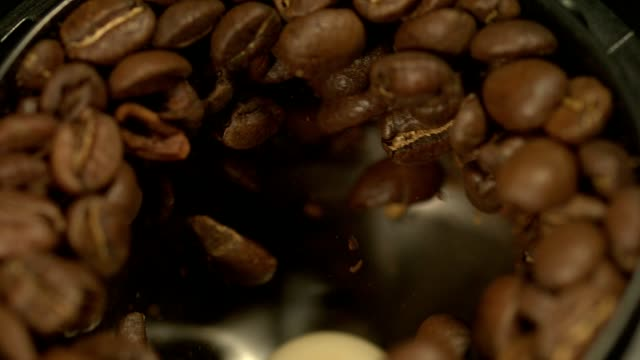 fresh roasted arabica coffee beans in coffee grinder @1500fps closeup shot - abundance stock videos & royalty-free footage