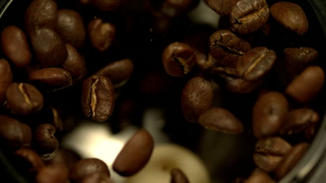 fresh roasted arabica coffee beans in coffee grinder @1500fps closeup shot