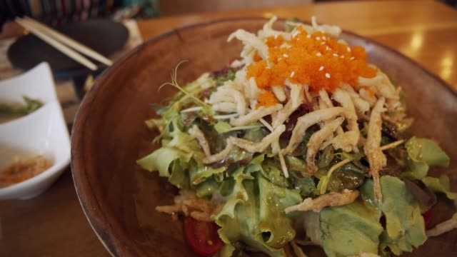 Fresh salad with white small Japanese fish on a wooden bowl