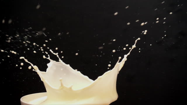 a fresh strawberries falls into a bowl of milk creating a splash in slow motion.  the camera revolves around the splash capturing the spectacular moment in a way never before captured. - david ewing stock videos & royalty-free footage
