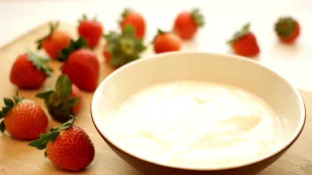 Fresh strawberries splashing into yogurt