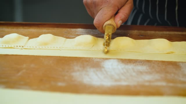 fresh stuffed pasta cut with cutter wheel - italian culture stock-videos und b-roll-filmmaterial