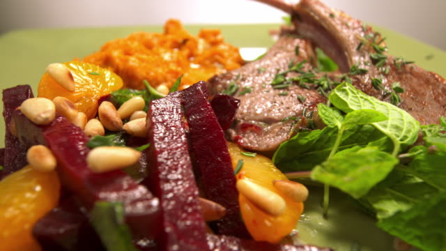 fresh thyme falls onto a rotating dinner plate holding lamb chops, mashed sweet potatoes, beets, and pine nuts. - lammkotelett stock-videos und b-roll-filmmaterial