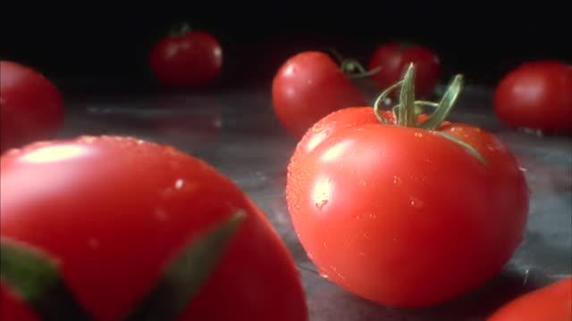 fresh tomatoes tumble onto a granite counter top. - tomato stock videos & royalty-free footage