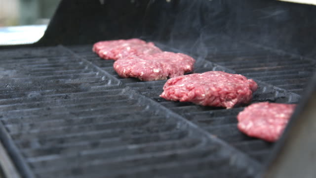 fresh uncooked pink local ground beef hamburgers cooking for dinner on the grill in the summer - raw food stock videos & royalty-free footage