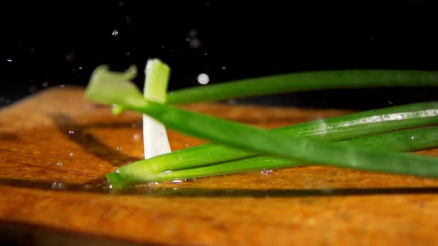 hd slow motion: fresh wet spring onions - scallion stock videos & royalty-free footage