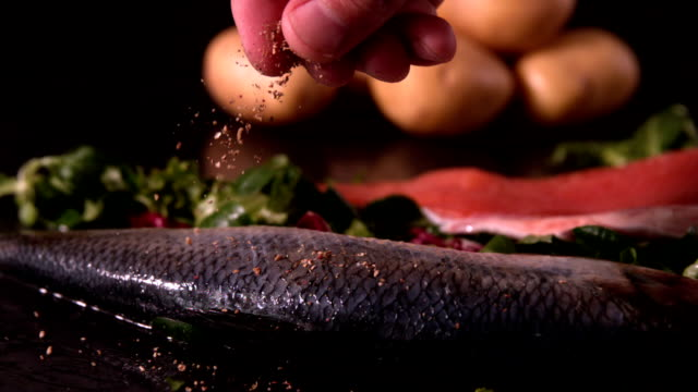 fresh whole trout on a bed of leaves being seasoned - pepper seasoning stock videos and b-roll footage