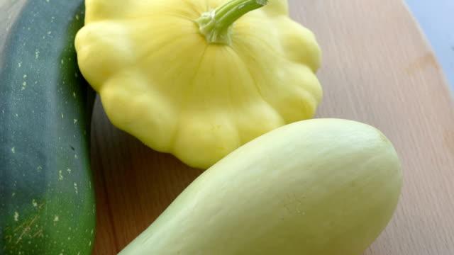 Fresh zucchini, squash, marrow squash on the wooden plate