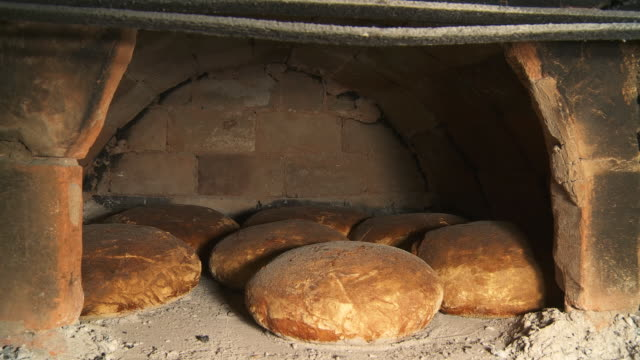 hd dolly: fresh-baked loaves in brick oven - peasant bread stock videos and b-roll footage