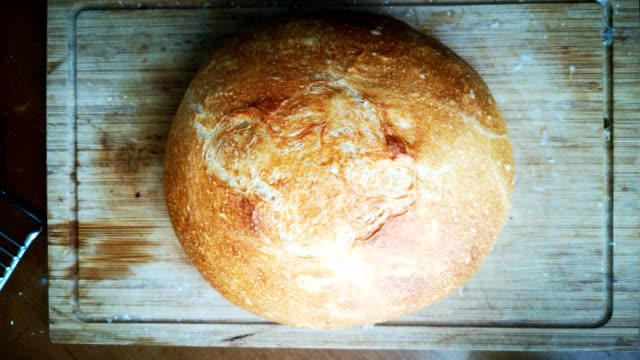 freshly baked bread boule on wooden cutting board - pane a lievito naturale video stock e b–roll