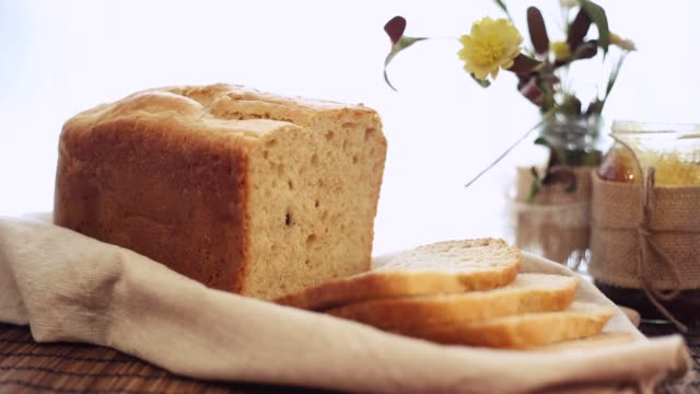 a freshly baked bread sliced next to a jar of honey - pane in cassetta video stock e b–roll
