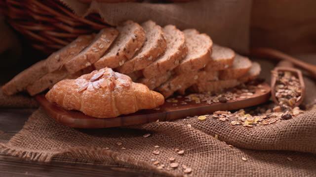 stockvideo's en b-roll-footage met vers gebakken heerlijk brood op een rustiek houten werkblad met exemplaarruimte, gezond het eten concept. - volkorentarwe