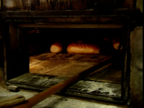 vídeos y material grabado en eventos de stock de freshly baked loaves of bread are removed from oven - al horno