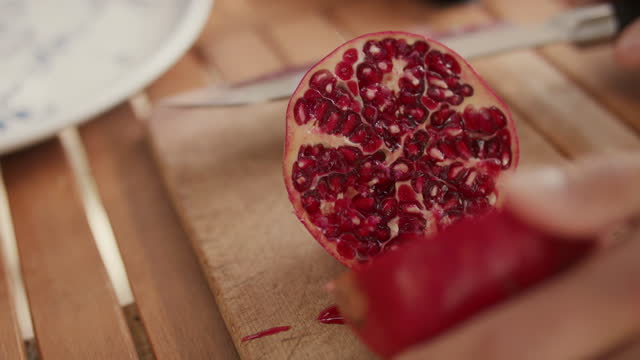 freshly cut pomegranate on wooden cutting board - antioxidant stock videos & royalty-free footage
