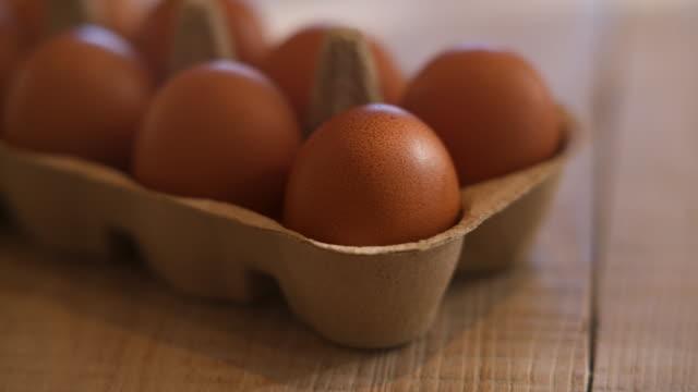 vídeos y material grabado en eventos de stock de freshly laid organic brown hen eggs in recyclable brown cardboard egg tray on wooden farm table - grupo mediano de objetos