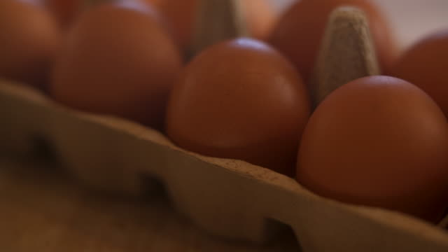 vidéos et rushes de freshly laid organic brown hen eggs in recyclable brown cardboard egg tray on wooden farm table - groupe moyen d'objets