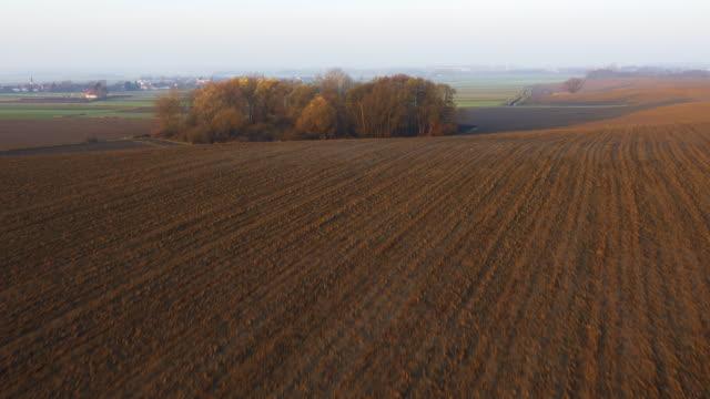 aerial frisch gepflügtes feld mit ländlichen landschaft - pflügen stock-videos und b-roll-filmmaterial