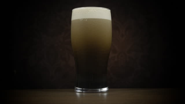 freshly poured pint of stout zoom out - pint glass stock videos & royalty-free footage