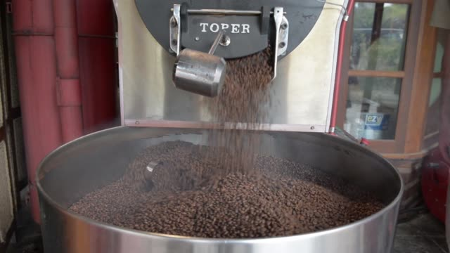 freshly roasted coffee beans fall from a roaster at the skybury coffee pty coffee plantation in the atherton tablelands queensland australia on... - ugnsstekt bildbanksvideor och videomaterial från bakom kulisserna