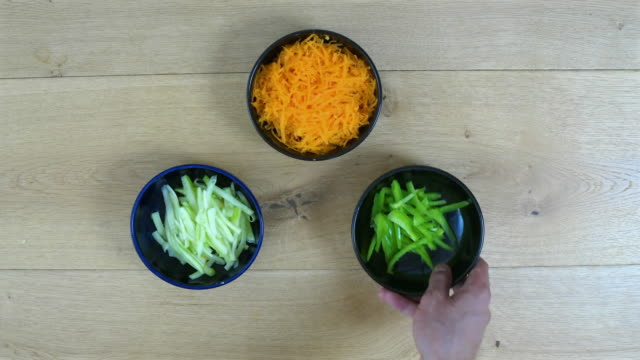 vídeos y material grabado en eventos de stock de freshly shredded cut vegetables, orange carrot, cucumber, green capsicum, being placed on a table in separate bowls - carrot top