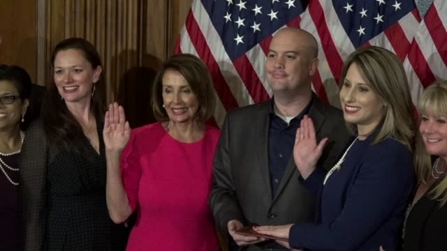 freshman california congresswoman katie hill is administered the oath of office in ceremony by house speaker nancy pelosi among family as media snap... - hill点の映像素材/bロール