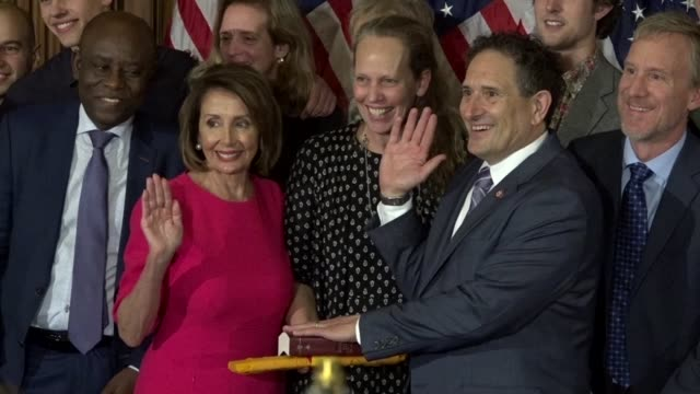freshman michigan congressman andy levin is administered the oath of office in ceremony by house speaker nancy pelosi among family as media snap... - membro del congresso video stock e b–roll