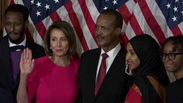 freshman minnesota congresswoman ilhan omar is administered the oath of office in ceremony by house speaker nancy pelosi among family as media snap... - eid stock-videos und b-roll-filmmaterial