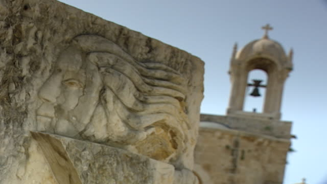vidéos et rushes de friary and church of saint johnmark angled cu of a modern carved relief with the church bell tower in the background - clocher élément architectural