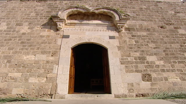 vídeos de stock e filmes b-roll de friary and church of saint john-mark. low angle view of the side door of the medieval church. - frontão triangular