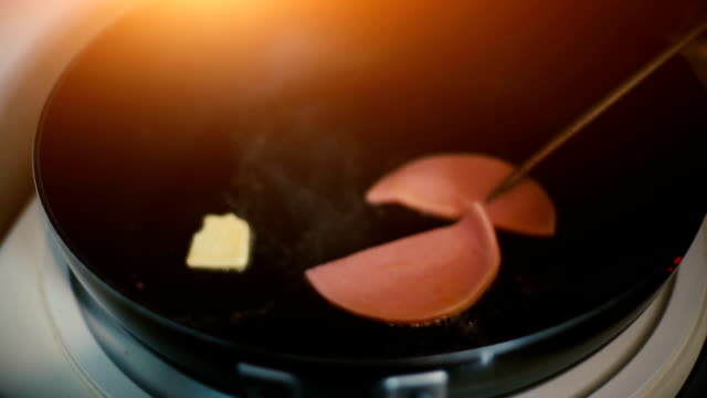 Fried bologna in frying pan for making a sandwich.