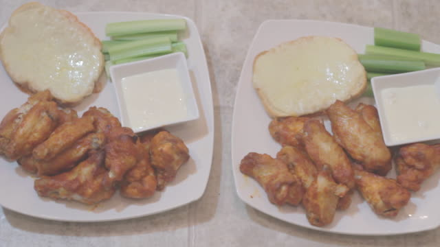 fried chicken pieces on 2 white plates, celery, half bagle & dip  2 - celery stock videos and b-roll footage