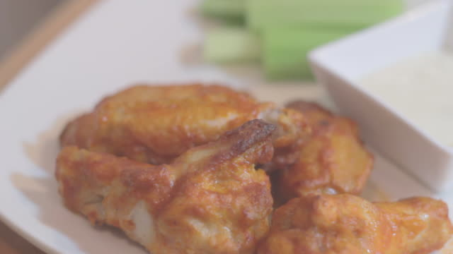 Fried chicken pieces on white plate, celery and dip in background 1