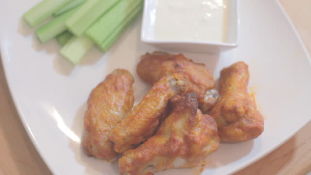 fried chicken pieces on white plate, celery and dip in background 5 - celery stock videos and b-roll footage