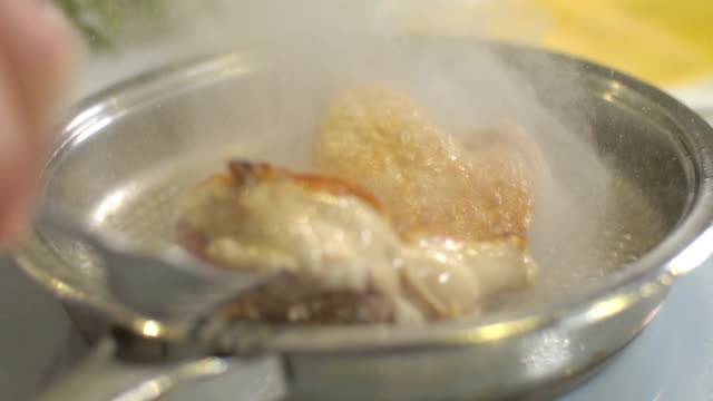 Fried chicken with oil that is boiling, slow motion
