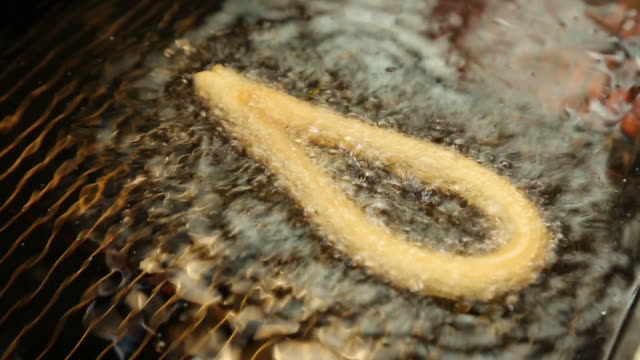 fried churros dough in oil - churro stock videos & royalty-free footage