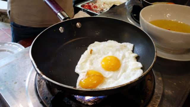 stockvideo's en b-roll-footage met gebraden ei op een varken-ijzer koekenpanvoorbereidingsproces - gebakken ei