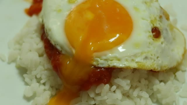 Fried egg with white rice and tomato sauce on dish.