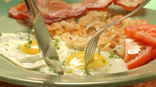 vídeos y material grabado en eventos de stock de cu fried eggs sunny side up on breakfast plate served with hash browns and a strip of bacon as fork and knife split open the egg yolk and a slice of bread is dipped into egg yolk - huevos fritos de un solo lado