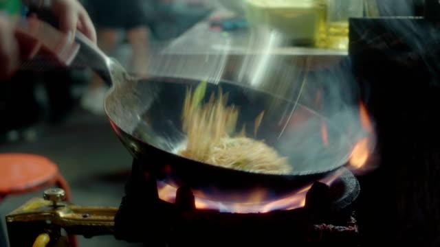 vídeos de stock, filmes e b-roll de macarrão frito no mercado noturno - sala de jantar