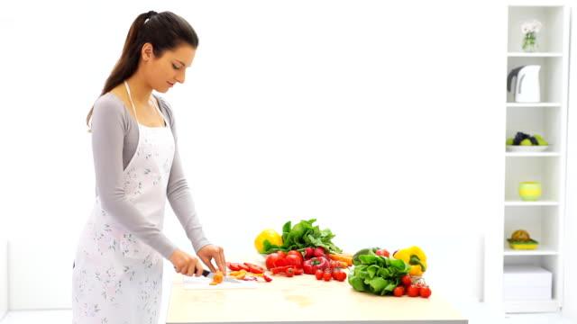 ・フライドリーキッチンの女性カティング野菜ます。 - ジェンダー・ステレオタイプ点の映像素材/bロール