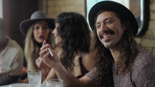 friend across the table offers hip young man an electronic cigarette in crowded austin bar at happy hour. - foodie stock videos & royalty-free footage