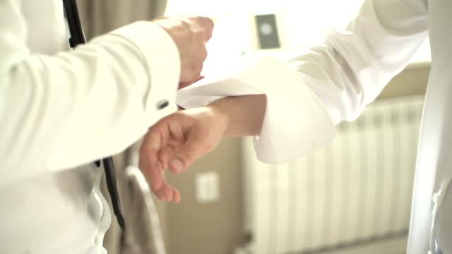 MEDIUM SHOT Friend fastening groom's cuff