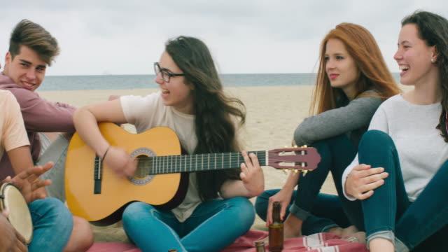 Amigo tocando música en la playa