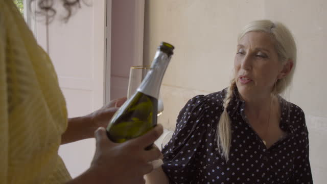 a friend pours champagne for an adult woman. - 50 59 years stock videos & royalty-free footage