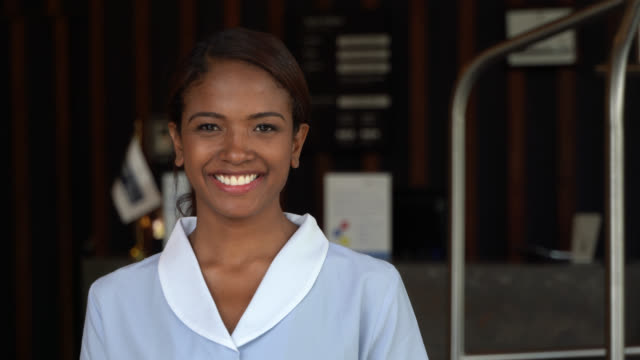 friendly african american house keeper smiling at camera while working at a hotel - housework stock videos & royalty-free footage