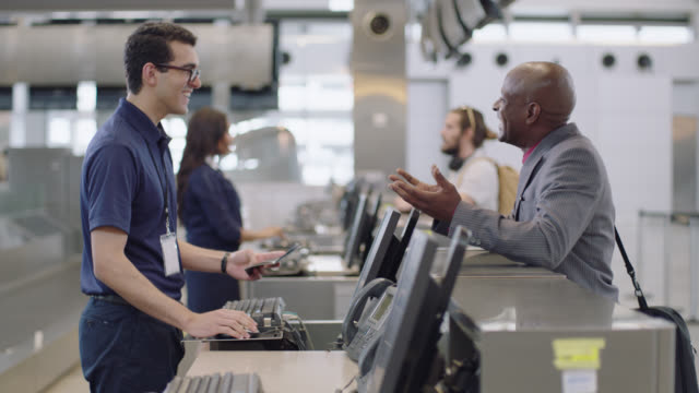 vídeos de stock, filmes e b-roll de friendly airline employee takes smiling business traveler's passport at check-in counter in airport terminal. - avião comercial