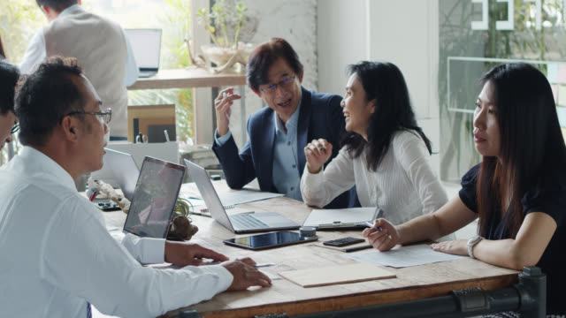 friendly asian businesspeople working together and chatting in coworking space - coworking space stock videos and b-roll footage